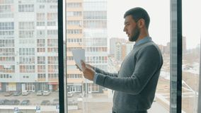 Young businessman is looking startup project, standing by window in company. stock video footage