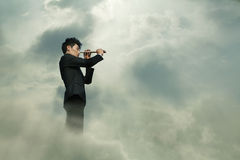 Young businessman looking through telescope in a dreamlike cloud Royalty Free Stock Photos