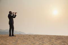 Young businessman looking through telescope in the middle of the desert royalty free stock image