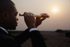 Young businessman looking through telescope in the middle of the desert stock photos
