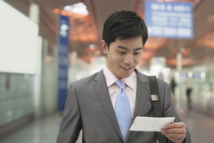 Young businessman looking at ticket at the airport, Beijing, China Royalty Free Stock Photo