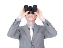 Young businessman looking up through binoculars Royalty Free Stock Photo