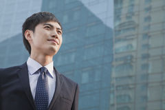 Young Businessman Looking Up, Glass Building,  Portrait Stock Image