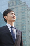 Young Businessman Looking Up, Glass Building, Portrait Royalty Free Stock Photo
