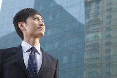 Young Businessman Looking Up, Glass Building, Portrait Royalty Free Stock Photography