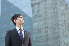 Young Businessman Looking Up, Glass Building,  Portrait Stock Images