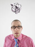 Young businessman looking up at piggy bank tied with rope representing trapped finances Royalty Free Stock Photography