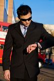 Young businessman looking at wristwatch. Outdoors Royalty Free Stock Image