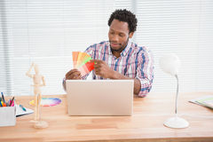 Young businessman looks at colourful cards Stock Photography
