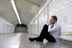 Young businessman lost in depression sitting on ground street subway Royalty Free Stock Photo