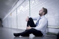 Young businessman lost in depression sitting on ground street subway Stock Photography