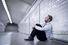 Young businessman lost in depression sitting on ground street subway Stock Photos