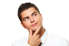 Young businessman lost in thoughts. A portrait of a young businessman lost in thoughts over white background Royalty Free Stock Images