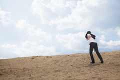 Young businessman lost and walking through the desert Stock Photo