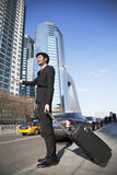Young Businessman with luggage on the street hailing a cab Stock Photography