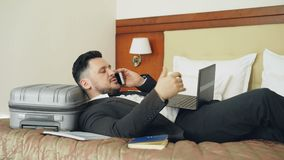 Young businessman lying on bed and suitcase talking phone and working with laptop from his hotel room. Travel, business. Young bearded businessman lying on bed stock footage