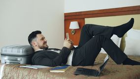Young businessman lying on bed and suitcase using smartphone while resting after arrival at hotel room. Travel, business. Young bearded businessman lying on bed stock footage