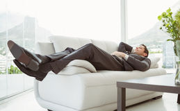Young businessman lying on couch Stock Photos