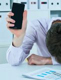 Young businessman lying on the desk in office showing blank screen of smartphone, keeping face on his hands. Deadline. Young businessman lying on the desk in Stock Photo