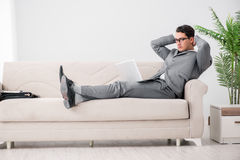 The young businessman lying on the sofa Stock Image