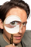 Young businessman with a magnifying glass Royalty Free Stock Images
