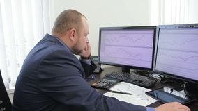 Young businessman makes call while sitting in modern office. Man is at table with computer, looks carefully at diagrams depicted on two monitors and talks with stock video