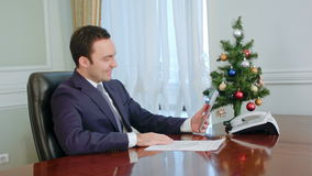 Young businessman makes call by tablet, smiling, congratulates with Christmas stock footage