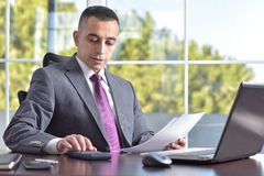 Young Businessman Making Calculations. At Table In His Office Stock Images
