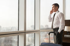 Young businessman making call in hotel room Royalty Free Stock Photography