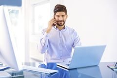 Young businessman making a call while working on laptop stock photo