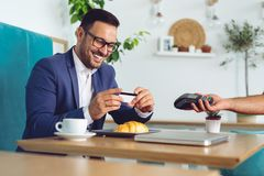 Businessman making contactless card payment in a cafe royalty free stock image