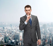 Young businessman making hush sign Stock Photos