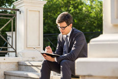 Young businessman making notes Stock Photo