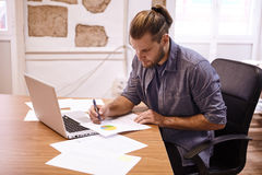Young businessman making notes at desk Royalty Free Stock Photos