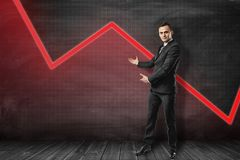 Young businessman making presenting gesture at red graphic polygonal curve behind him. royalty free stock photography