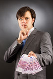 Young  businessman making silence gesture and holding euro bankn Royalty Free Stock Photo