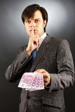 Young  businessman making silence gesture and holding euro bankn Royalty Free Stock Images