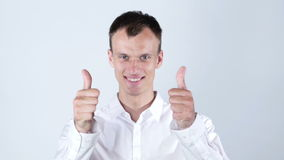 A young businessman making the thumbs up gesture over a white background. A young businessman making the thumbs up gesture isolated over a white stock video