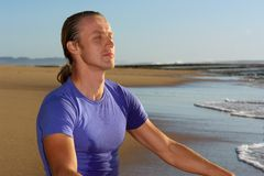 Young businessman meditates on beach Royalty Free Stock Photos