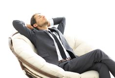 Young businessman meditating in big comfortable armchair. Photo with copy space Stock Image