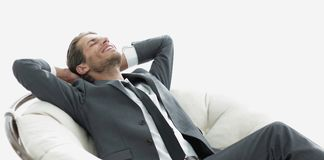 Young businessman meditating in big comfortable armchair. Photo with copy space Stock Images