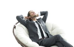 Young businessman meditating in big comfortable armchair. Photo with copy space Royalty Free Stock Images