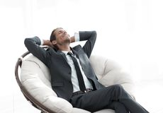 Young businessman meditating in big comfortable armchair. Photo with copy space Royalty Free Stock Photos