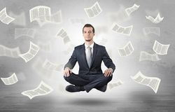 Businessman meditating with flying paper concept stock photos
