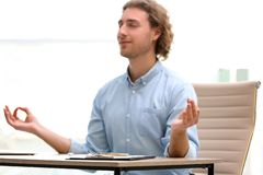 Young businessman meditating at table in office during break. Zen yoga. Young businessman meditating at table in office during break, space for text. Zen yoga royalty free stock image