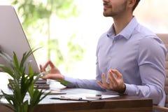 Young businessman meditating at workplace. Zen concept. Young businessman meditating at workplace, closeup. Zen concept royalty free stock photos