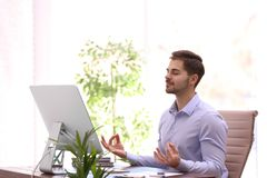 Young businessman meditating at workplace. Zen concept stock images