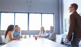 Young businessman on a meeting with office workers on a room background. Technology concept. Copy space. royalty free stock photos