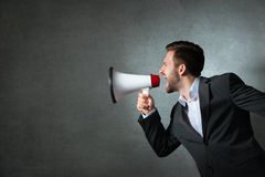 Young businessman with a megaphone royalty free stock photo