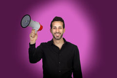 Young businessman with a Megaphone proclaiming something. On purple background Royalty Free Stock Image